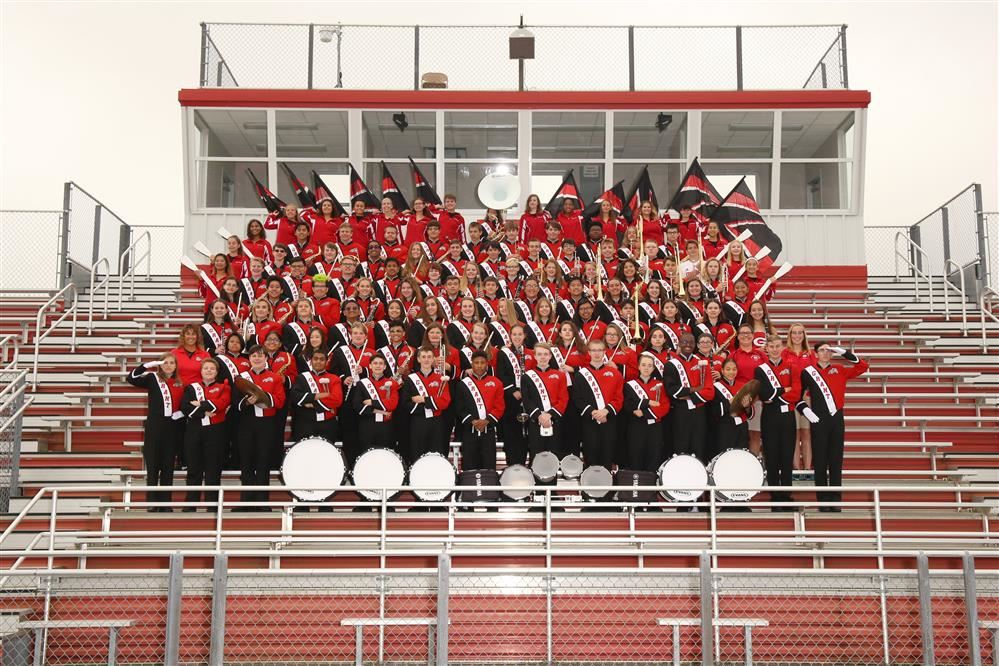 Grant Community High School Marching Band group photo on football stadium bleachers