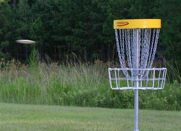Flying disc approaching disc golf target